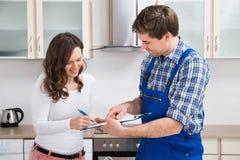 Scrittura della donna sulla lavagna per appunti con l'idraulico In Kitchen Room immagine stock