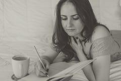Scrittura della donna in suo taccuino Fotografia Stock