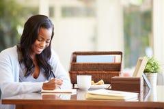 Scrittura della donna in taccuino che si siede allo scrittorio Fotografia Stock