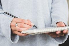 Scrittura della donna in taccuino di carta Fotografie Stock