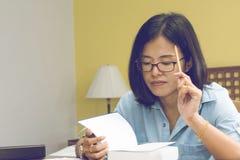 Scrittura della donna in un libro con una matita fotografie stock