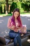 Scrittura della donna in un taccuino che si siede su un banco di legno nel parco Ragazza che lavora all'aperto sul computer porta Immagini Stock Libere da Diritti