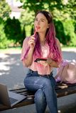 Scrittura della donna in un taccuino che si siede su un banco di legno nel parco Ragazza che lavora all'aperto sul computer porta Fotografia Stock