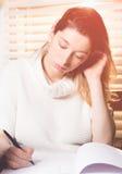 Scrittura della donna in un taccuino con una penna Immagine Stock Libera da Diritti