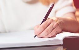 Scrittura della donna in un taccuino con una penna Fotografia Stock