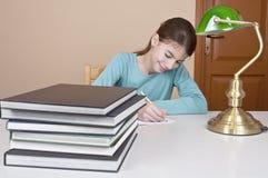 Scrittura della giovane donna con i libri Fotografie Stock Libere da Diritti