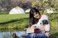 Scrittura della giovane donna con il suo cane in un parco di autunno Fotografie Stock Libere da Diritti