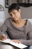 Scrittura della giovane donna in libro Fotografia Stock