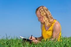 Scrittura della giovane donna nell'erba con cielo blu fotografia stock libera da diritti