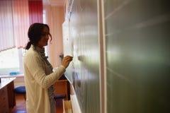 Scrittura della giovane donna su una lavagna che tiene le sue note nella classe A Fotografia Stock Libera da Diritti