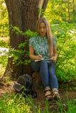 Scrittura della giovane donna in suo diario sull'erba con i fiori Fotografia Stock