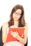 Scrittura della giovane donna in suo taccuino Fotografia Stock Libera da Diritti