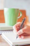 Scrittura della mano con il fondo verde della tazza Fotografie Stock