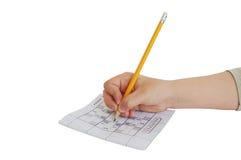 Scrittura della mano del bambino sul gioco di sudoku Immagine Stock