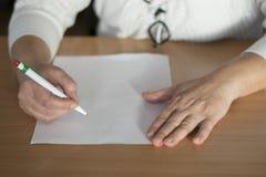 Scrittura della mano del ` s della donna del primo piano sulla carta Fotografia Stock Libera da Diritti