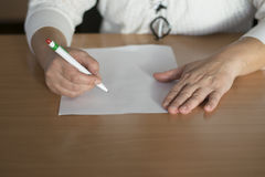 Scrittura della mano del ` s della donna del primo piano sulla carta Immagini Stock Libere da Diritti