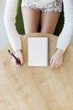 Scrittura della mano del ` s della donna in taccuino Fotografie Stock Libere da Diritti