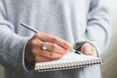 Scrittura della mano del ` s della donna in taccuino di carta Immagine Stock Libera da Diritti