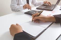 Scrittura della mano dell'uomo d'affari sul taccuino con le finanze che paning circa il costo e calcolatore e computer portatile  Immagini Stock Libere da Diritti