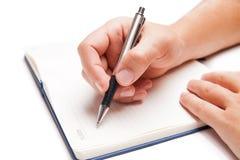 Scrittura della mano dell'uomo in libro aperto su bianco Fotografia Stock