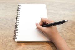 Scrittura della mano della donna sul taccuino Immagini Stock