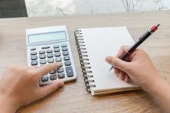 Scrittura della mano della donna sul taccuino con la matita ed il calcolatore Fotografie Stock Libere da Diritti