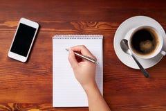 Scrittura della mano della donna in un blocco note fotografia stock