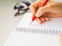 Scrittura della mano della donna del primo piano con il fondo rosso di vetro e della matita sulla tavola di funzionamento Fotografia Stock