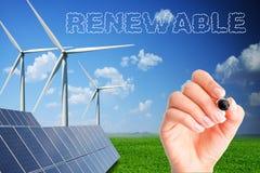 Scrittura della mano della donna rinnovabile sullo schermo trasparente con i generatori eolici ed i pannelli solari come fondo Immagini Stock