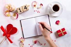 Scrittura della mano sul taccuino con l'innamorato Valentine Day Concept felice Immagini Stock