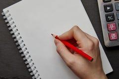 scrittura della mano sul taccuino con la matita rossa Fotografia Stock Libera da Diritti