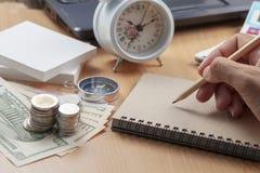 Scrittura della matita di uso della mano sulla nota della carta e sul posto di lavoro di affari degli oggetti di finanza di affar fotografie stock libere da diritti