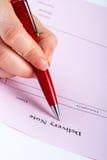 Scrittura della nota di consegna in bianco con la penna immagine stock libera da diritti