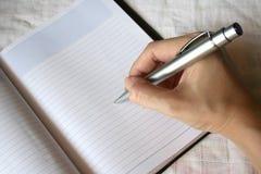 Scrittura della penna di holding della mano sul taccuino Fotografia Stock Libera da Diritti