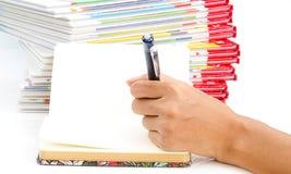 Scrittura della penna di tenuta della mano della donna sul libro Immagini Stock