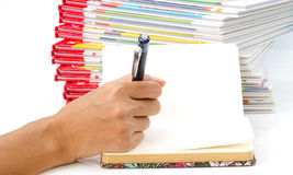 Scrittura della penna di tenuta della mano della donna sul libro Immagini Stock Libere da Diritti