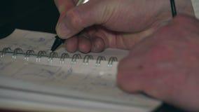 Scrittura della penna in un taccuino archivi video