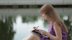Scrittura della ragazza dalla riva del fiume video d archivio