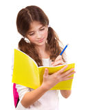 Scrittura della ragazza della scuola in taccuino Fotografia Stock Libera da Diritti