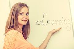 Scrittura della ragazza dello studente che impara parola sulla lavagna Fotografia Stock