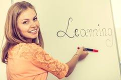 Scrittura della ragazza dello studente che impara parola sulla lavagna Immagini Stock