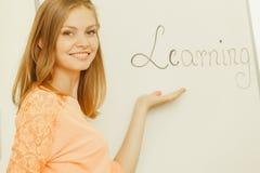 Scrittura della ragazza dello studente che impara parola sulla lavagna Fotografie Stock Libere da Diritti