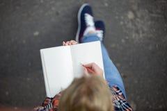 Scrittura della ragazza dello studente con una matita in un taccuino Immagine Stock Libera da Diritti