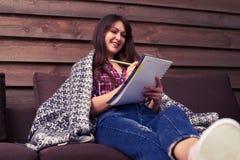 Scrittura della ragazza di Smilling in un taccuino mentre sedendosi sul sofà a Fotografie Stock