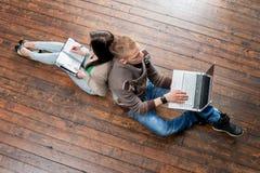 Scrittura della ragazza nel taccuino e nel ragazzo che per mezzo di un computer portatile Fotografia Stock