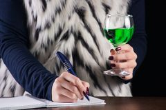 Scrittura della ragazza nella bevanda dell'alcool dell'assenzio delle tenute e del taccuino a disposizione fotografia stock
