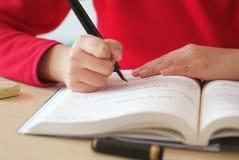 Scrittura della ragazza per lo studio Immagine Stock