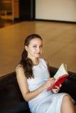 Scrittura della ragazza in schizzo-libro e guardare in camera Fotografie Stock