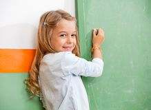 Scrittura della ragazza sulla lavagna verde in aula Fotografia Stock