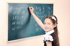 Scrittura della ragazza sulla scheda dell'aula Immagini Stock Libere da Diritti